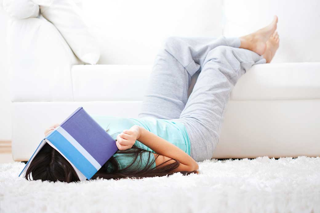 Young woman lying on floor with feet on sofa and book over face in resignation